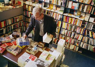 Mature man looking at books in bookstore